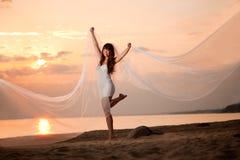 有长的面纱的美丽的新娘在日落的海滩 免版税库存图片