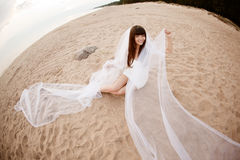 有长的面纱的美丽的新娘在日落的海滩 免版税库存照片