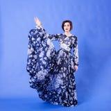 有长的飞行礼服的华美的妇女在蓝色背景 库存图片
