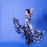 有长的飞行礼服的华美的妇女在蓝色背景 免版税库存照片
