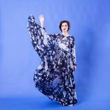 有长的飞行礼服的华美的妇女在蓝色背景 免版税库存图片