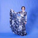 有长的飞行礼服的华美的妇女在蓝色背景 库存照片