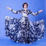 有长的飞行礼服的妇女在蓝色背景 免版税库存照片