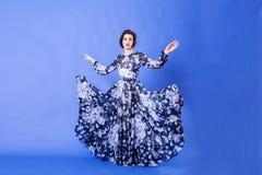 有长的飞行礼服的美丽的妇女在蓝色背景 免版税图库摄影