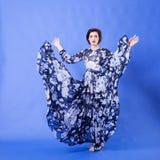 有长的飞行礼服的美丽的妇女在蓝色背景 免版税库存照片