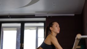 有长的马尾辫的微笑的女孩舞蹈家在黑贴身衬衣占去芭蕾纬向条花扶手栏杆并且提出腿慢动作 影视素材
