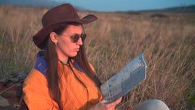 有长的黑发的一个女孩在一个救生服、一个皮革牛仔帽和玻璃坐,看旅客s地图 影视素材