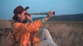 有长的黑发的一个女孩在一个救生服和一个皮革牛仔帽在草坐,看通过望远镜 股票录像