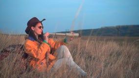 有长的黑发的一个女孩在一个救生服和一个皮革牛仔帽在草坐,看通过望远镜 影视素材