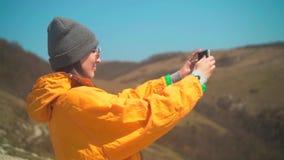 有长的黑发的一个女孩在一个救生服,一个灰色盖帽,玻璃在山在电话站立并且做照片 股票录像