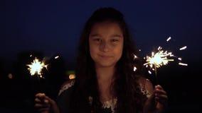 有长的黑发的一个女孩在晚上拿着烟花并且高兴 慢的行动 影视素材