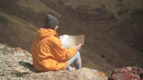 有长的黑发的一少女在一个救生服和一个灰色盖帽在山和神色坐在旅游地图 影视素材