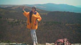 有长的黑发的一少女在一个救生服和一个灰色盖帽在山站立并且采取在电话的一selfie 股票录像