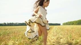 有长的黑发的女孩横跨倾斜的麦子的领域跑 容量礼服的美丽的女孩跑  股票视频