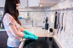 有长的黑发的年轻女人清洗一个黑烹饪器材盘区 图库摄影