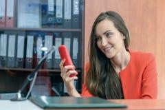 有长的黑发的美丽的妇女在一套红色衣服拜访电话的 秘书虚度光阴在工作 免版税库存照片