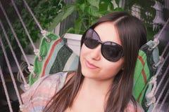 有长的黑发的美女在太阳镜休息在一个吊床的开会在阳台 库存图片
