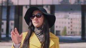 有长的黑发的美女在帽子步行沿着向下街道离开他的玻璃和神色入照相机 股票录像