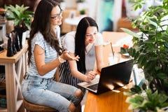 有长的黑发的,佩带的便装样式两个逗人喜爱的微笑的亭亭玉立的女孩,坐在桌上并且看殷勤地膝上型计算机 免版税库存照片