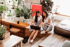 有长的黑发的,佩带的偶然成套装备两个年轻微笑的女孩,紧挨着坐和喝在舒适的咖啡 免版税库存照片