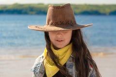 有长的黑色头发的美女在海滩的一个牛仔帽在一好日子 免版税库存照片