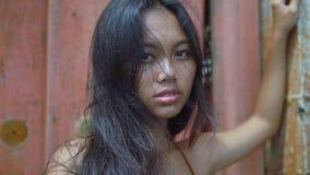 有长的黑色头发立场的俏丽的亚裔女孩在红色背景,看凸轮 股票录像