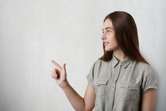 有长的黑发、好的站立斜向一边在灰色背景的眼睛和迷人的微笑的一个相当女孩穿灰色T恤杉po 库存照片
