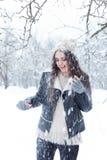 有长的黑发乐趣步行的美丽的少妇在冬天森林和使用与在一个冬天帽子的雪在一件黑夹克 库存照片