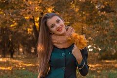 有长的头发和一条温暖的围巾的快乐的美丽的女孩在他的手微笑保留它的叶子 库存图片