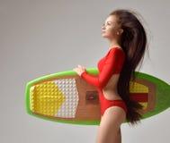 有长的头发和冲浪板的美丽的深色的少妇 图库摄影