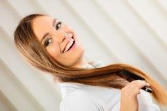 有长的头发和刷子的美丽的妇女 免版税图库摄影