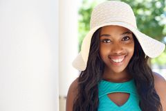 有长的头发和太阳帽子的愉快的年轻黑人女孩 库存图片