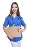 有长的黑发和文件的可爱的护士 免版税图库摄影