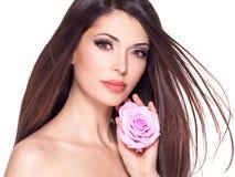 有长的头发和桃红色玫瑰的美丽的俏丽的妇女在面孔 图库摄影