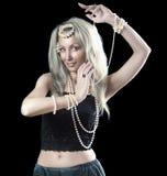 有长的头发和珍珠的白肤金发的妇女跳舞一个东方舞蹈 免版税图库摄影