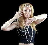 有长的头发和珍珠的美丽的年轻白肤金发的妇女跳舞一个东方舞蹈 图库摄影