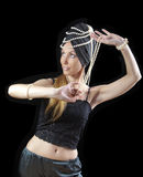 有长的头发和珍珠的美丽的年轻白肤金发的妇女跳舞在黑暗的背景的一个东方舞蹈 免版税图库摄影
