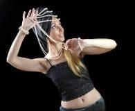有长的头发和珍珠的美丽的年轻白肤金发的妇女跳舞在黑暗的背景的一个东方舞蹈 库存照片