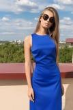 有长的头发在太阳镜和明亮的构成的美丽的典雅的时髦时髦的女孩在摆在为照相机的蓝色礼服  库存照片