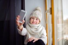 有长的头发坐的单独近的窗口的逗人喜爱的女孩与手机 免版税库存照片