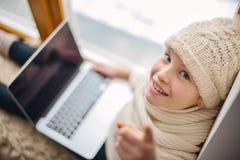 有长的头发坐的单独近的窗口的逗人喜爱的女孩与膝上型计算机 免版税库存图片