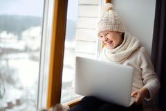 有长的头发坐的单独近的窗口的逗人喜爱的女孩与膝上型计算机 库存照片