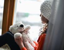 有长的头发坐的单独近的窗口的逗人喜爱的女孩在窗台 免版税库存图片