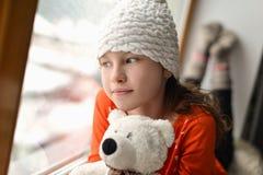 有长的头发坐的单独近的窗口的逗人喜爱的女孩在窗台 库存照片