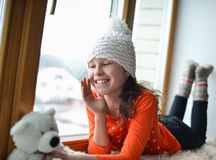 有长的头发坐的单独近的窗口的逗人喜爱的女孩在窗台 免版税库存照片