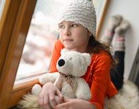 有长的头发坐的单独近的窗口的逗人喜爱的女孩在窗台 图库摄影