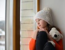 有长的头发坐的单独近的窗口的逗人喜爱的女孩在窗台 库存图片