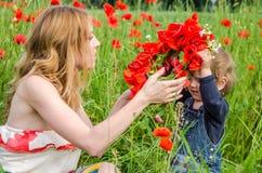 有长的头发妈妈的年轻迷人的妇女有她的走在草中的领域的女儿的,编织了一个花圈,红色po花束  免版税库存图片