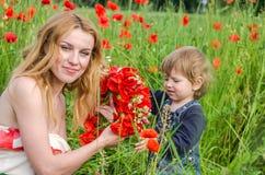 有长的头发妈妈的年轻迷人的妇女有她的走在草中的领域的女儿的,编织了一个花圈,红色po花束  免版税库存照片