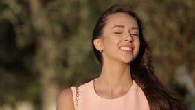 有长的黑发常设外部的俏丽的女孩在刮风的天气和微笑 影视素材